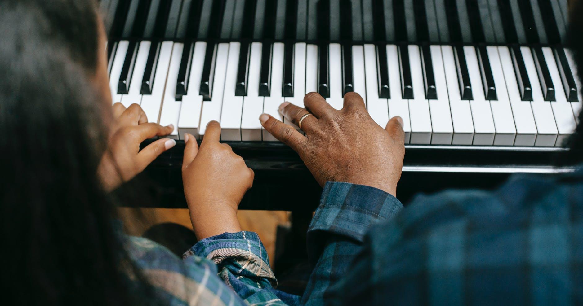 deux personnes entrain de jouer du piano